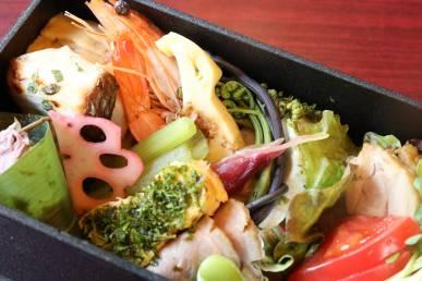 『十一口の厳選懐石弁当』の上段の一例。海老や魚料理など。